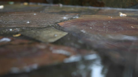 Rain falls on a stone sidewalk Footage