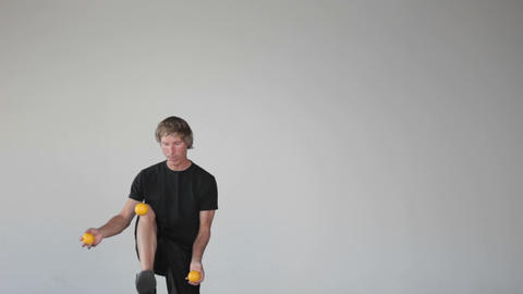 A man juggles three orange balls using both his hands and his legs Footage