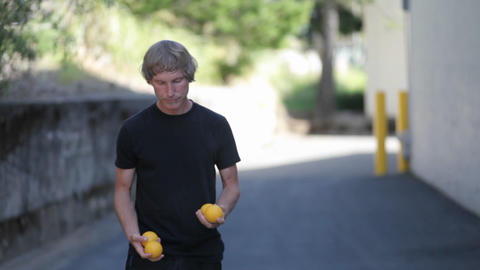 A man does a juggling act with four orange balls Stock Video Footage