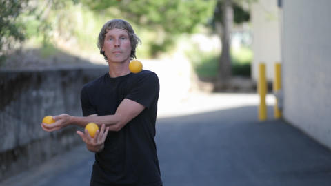 A man does a juggling act with four orange balls Footage