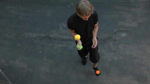 A man juggles three colored balls, using both his hands and his feet Footage