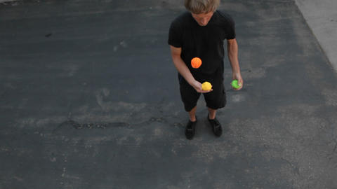 A man juggles three colored balls, using both his hands... Stock Video Footage