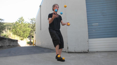 A man juggles five colored balls using his feet as well... Stock Video Footage