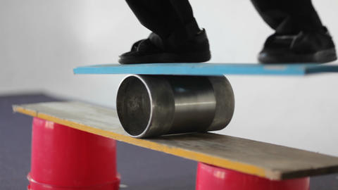 A man balances on a board set on top of a roller Footage