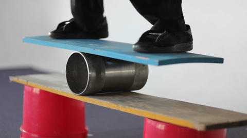 A man balances on a board set on top of a roller Stock Video Footage