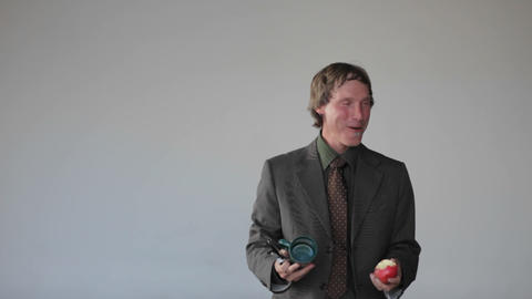A man does a juggling act with an apple, a cup and a... Stock Video Footage