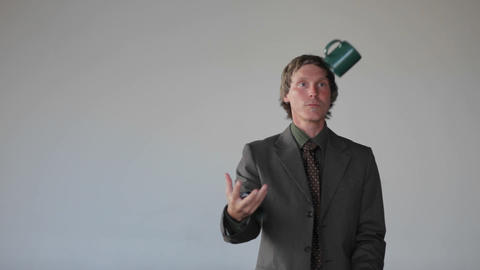 A man does a juggling act with an apple, a cup and a phone, answering the phone and catching the app Footage