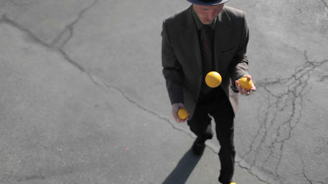A man does a juggling act in the street Footage