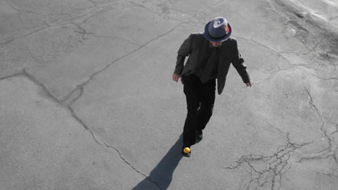 A man juggles an orange ball with his foot Stock Video Footage