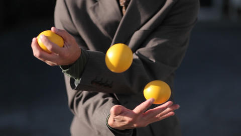 The man was effortlessly juggling 3 balls in the afternoon Footage