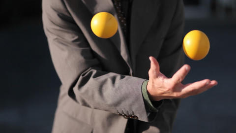 The man was effortlessly juggling 3 balls in the afternoon Stock Video Footage