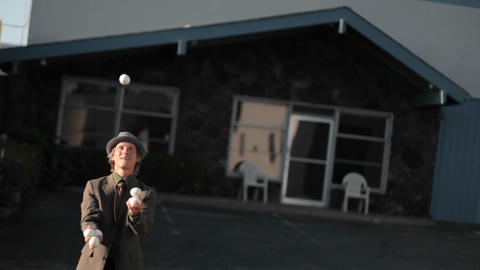 A man starts juggling a lot of balls and drops them all Stock Video Footage