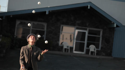 A man starts juggling a lot of balls and drops them all Footage