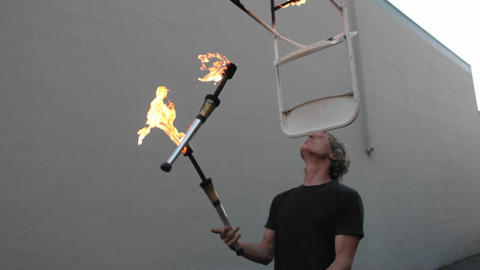 A street performer demonstrates his ability to juggle flaming torches whilst balancing a flaming cha Footage