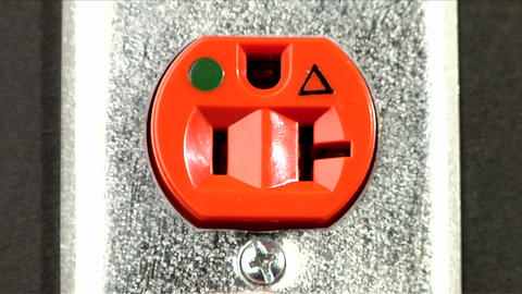 An orange electrical outlet sits in a wall Footage