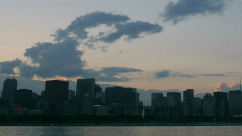 Wispy clouds pass over a city skyline at golden hour Stock Video Footage