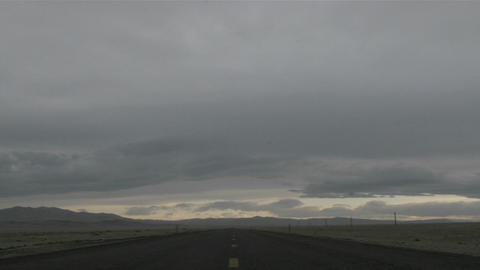 Gray storm clouds pass over a deserted highway Stock Video Footage