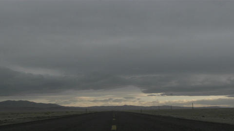 Gray storm clouds pass over a deserted highway Live Action