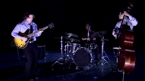 A band plays on a darkened stage Footage