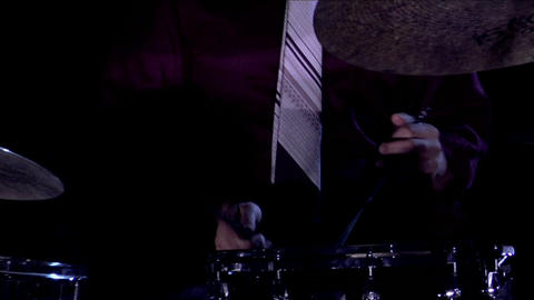 A drummer plays his drums on a darkened stage Stock Video Footage