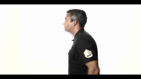 A police officer salutes then stands at ease Stock Video Footage