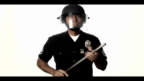 A police officer in riot gear thumps a baton in hi Stock Video Footage