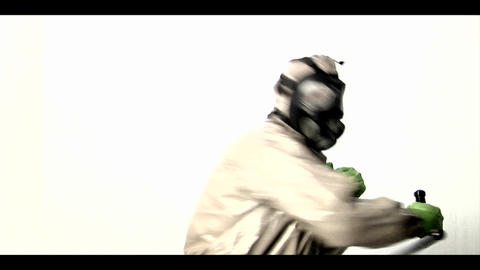 A man in a hazmat suit swings a police baton back  Footage
