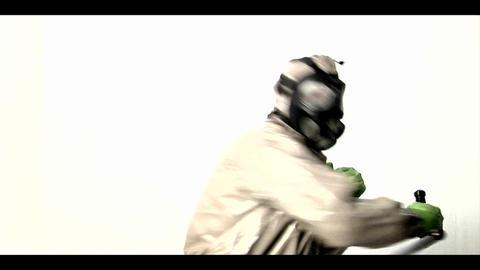 A man in a hazmat suit swings a police baton back Stock Video Footage