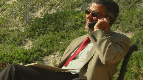 A businessman speaks on a cell phone from a patio Live Action