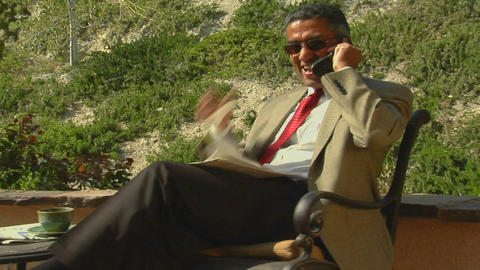 A businessman speaks on a cell phone from a patio Stock Video Footage