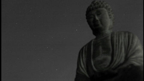 A starry sky passes over a stone Buddha Live Action