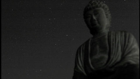 A starry sky passes over a stone Buddha Stock Video Footage