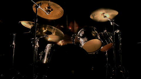 A drummer plays on a darkened stage Footage