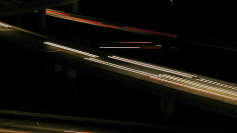 Cars drive on a freeway at night Footage