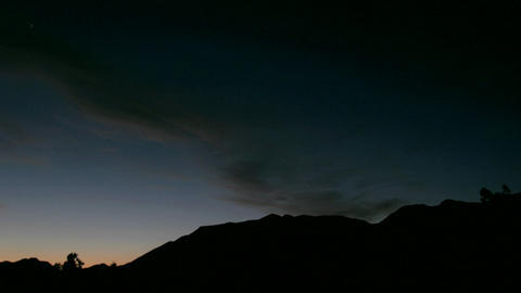 Clouds move over a silhouetted mountain during golden hour Stock Video Footage