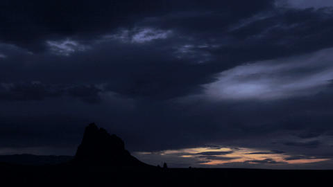 Clouds pass over a mountain at golden hour Stock Video Footage