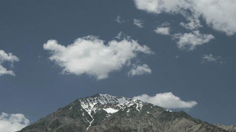 Clouds float over a snow-capped mountain peak Stock Video Footage