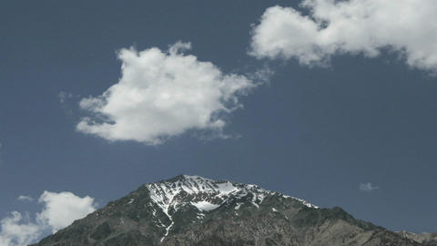 Clouds float over a snow-capped mountain peak Footage
