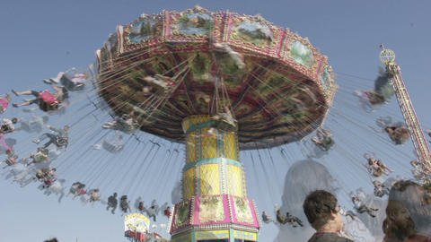 A swing ride at an amusement park spins as visitors pass... Stock Video Footage