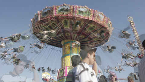 A swing ride at an amusement park spins as visitors pass below Live Action