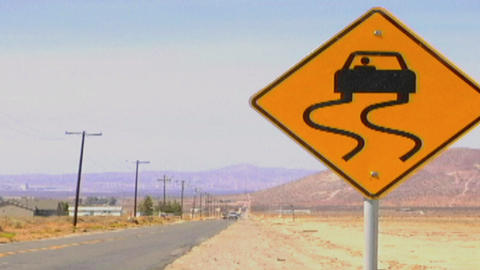 Cars pass by a curved road sign along a lonely desert highway Footage