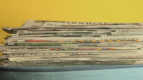 Newspapers stack up on a table Stock Video Footage