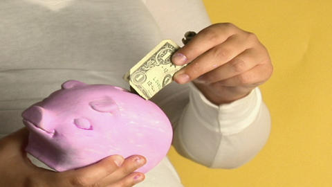 A woman places dollar bills into a piggy bank Stock Video Footage