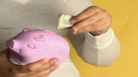 A woman places dollar bills into a piggy bank Footage