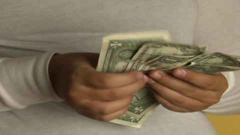 A woman counts dollar bills Stock Video Footage