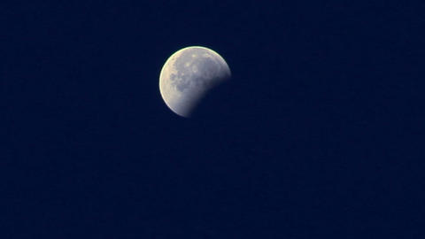 A three-quarters moon shines in a blue night sky Footage