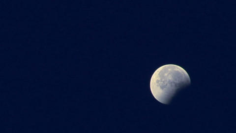 A three-quarters moon shines in a blue night sky Stock Video Footage