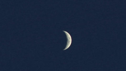 A crescent moon shines in a blue night sky Stock Video Footage