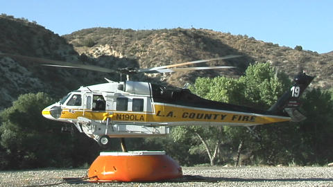 A fire fighting helicopter draws water in a mountain... Stock Video Footage