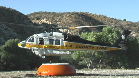 A fire fighting helicopter draws water in a mountain clearing Live Action